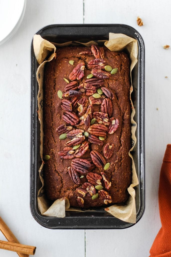 Sweet potato bread topped with pecans and pepitas in a loaf pan lined with parchment paper.