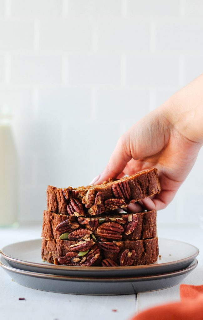 Hand grabbing a slice of vegan sweet potato bread stacked on a plate