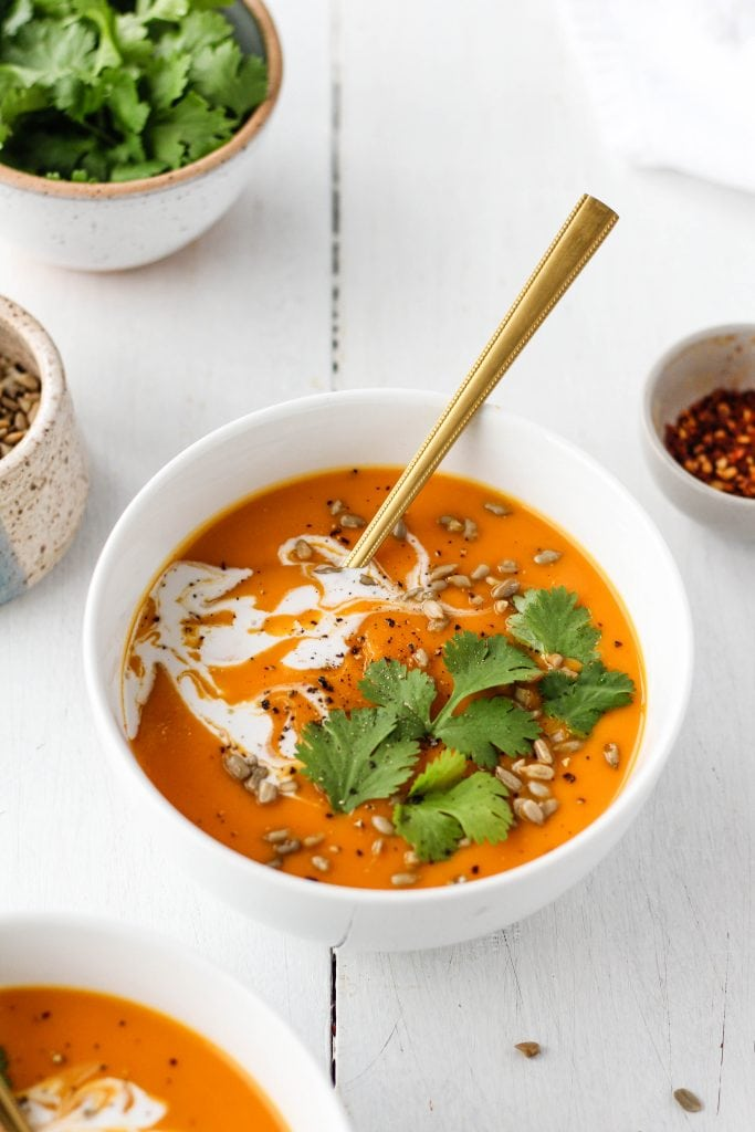 Spicy butternut squash and sweet potato soup in a white bowl garnished with cilantro, coconut cream and sunflower seeds.