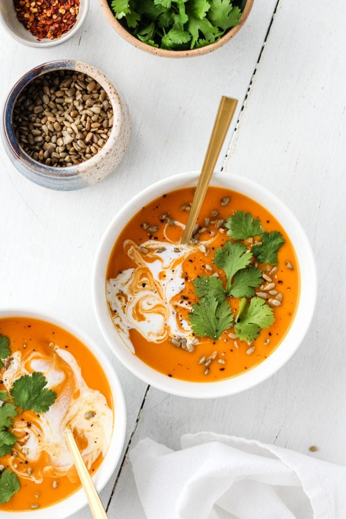 Two bowls of spicy butternut squash and sweet potato soup in a white bowl garnished with cilantro, coconut cream and sunflower seeds.