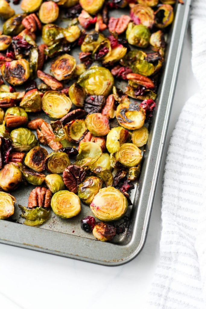 These easy balsamic roasted Brussels sprouts with pecans and cranberries are crispy and flavourful. Perfect for a healthy meal or holiday gathering. The ultimate vegan and gluten-free vegetable side dish!