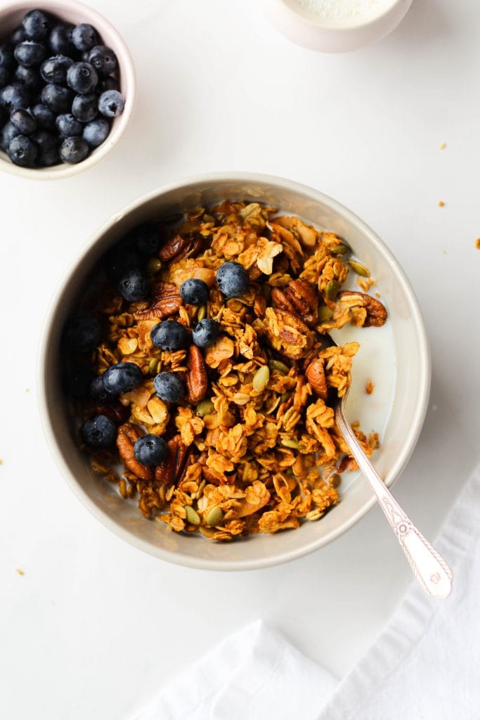 This healthy recipe for Vegan Pumpkin Granola easy to make, vegan and gluten-free. It's crunchy, clustery and loaded with good stuff like pecans, pumpkin seeds and coconut chips.