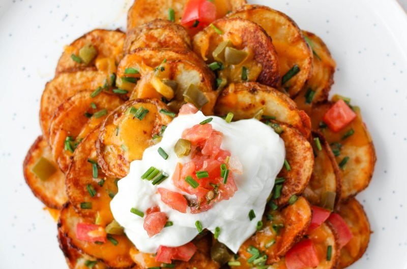 """This Irish Nachos recipe is simple and easy to make at home, but will remind you of your favourite Irish pub. The highlight of this recipe? Crisp on the outside, soft on the inside baked potato """"chips"""". Load them up with cheese, chopped veggies, sour cream and more!"""