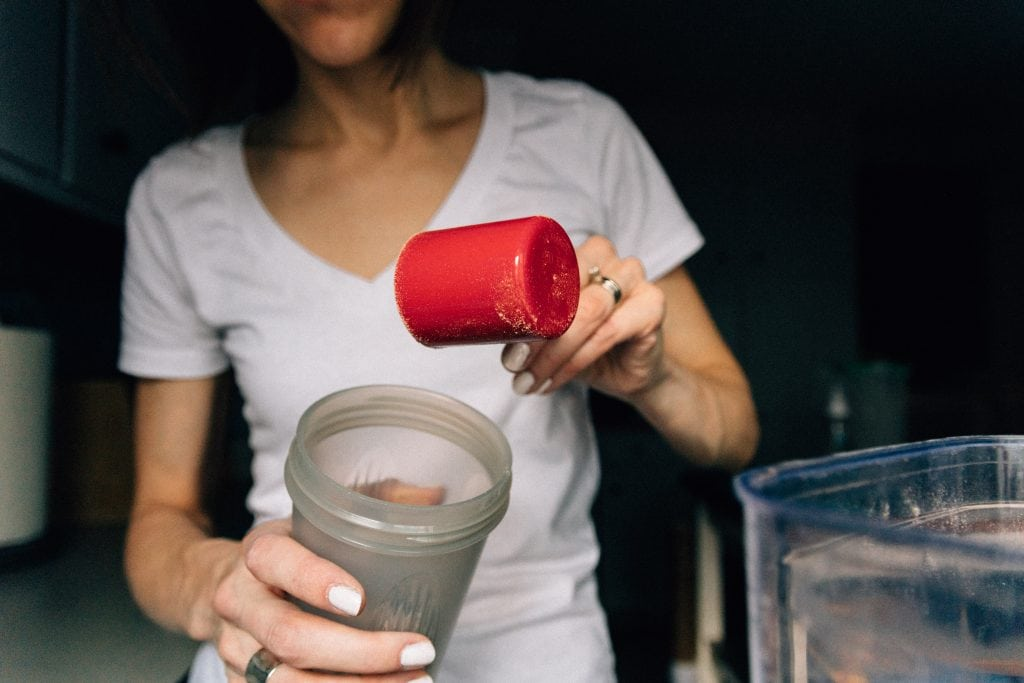 Woman adding protein powder to a shaker cup.