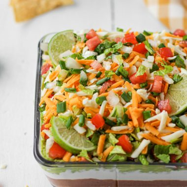 A 7-layer healthy bean dip layered with refried beans, greek yogurt, homemade guacamole, fresh Pico De Gallo, lettuce, cheese, and green onion with sliced lime for garnish.