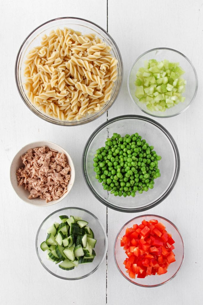 Healthy tuna pasta salad ingredients including rotini pasta, green peas, celery, red bell pepper, cucumber, and canned tuna.