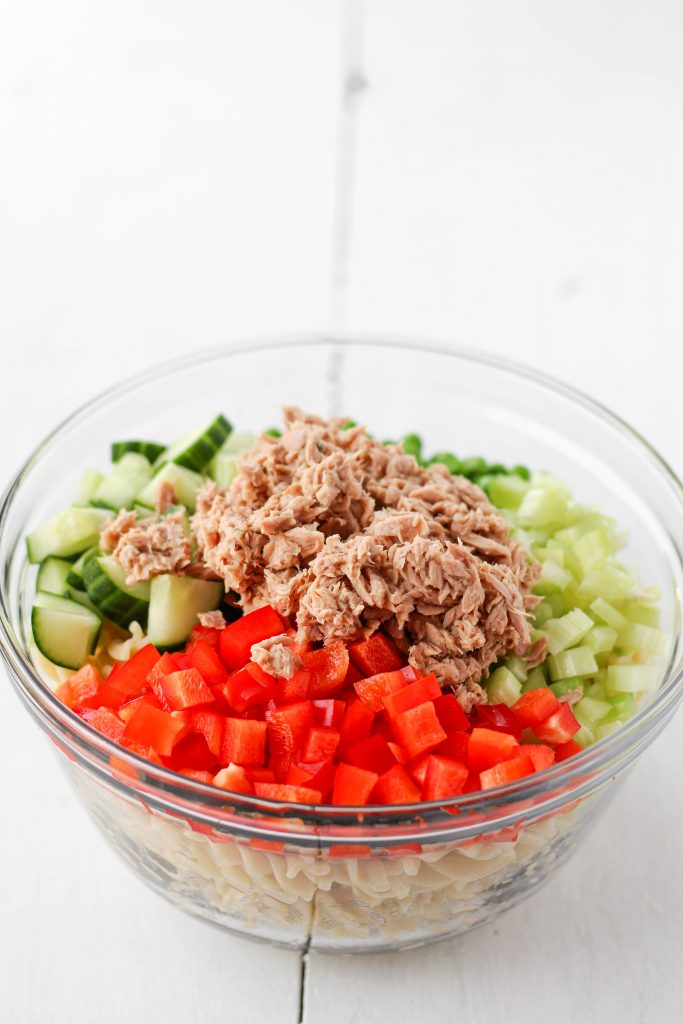 Large bowl with rotini, chopped vegetables, and tuna.