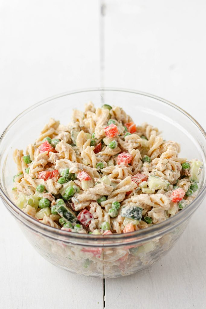 Large bowl with rotini, chopped vegetables, tuna and creamy dill dressing mixed together.
