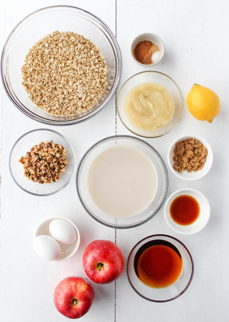 Ingredients for apple pie baked oatmeal laid out in bowls. Including oats, applesauce, walnuts, spices, eggs, milk, brown sugar, maple syrup, vanilla, lemon juice, and apples.