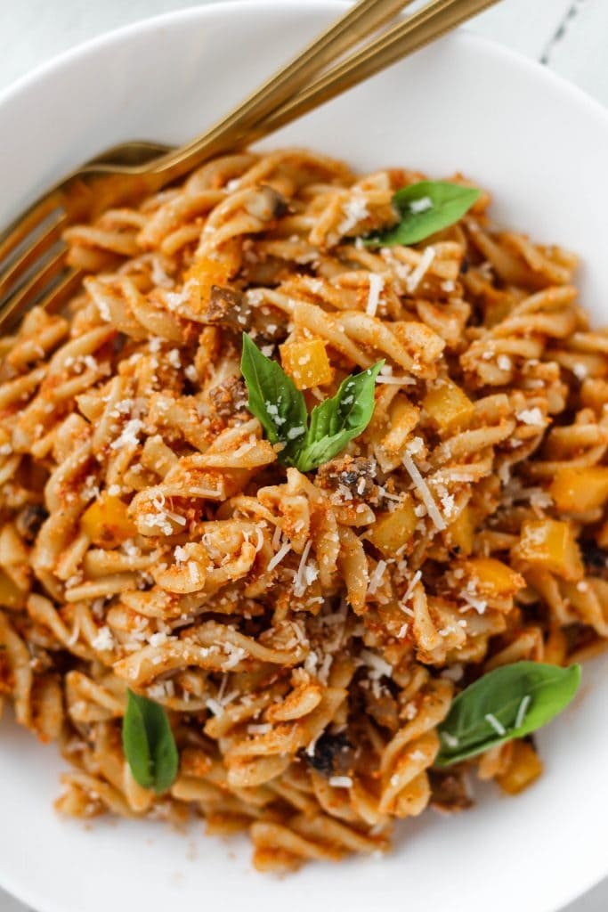 Sun-dried tomato pesto pasta in a bowl garnished with basil and parmesan cheese.