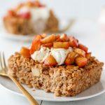 Apple Pie Baked Oatmeal on a plate topped with Greek yogurt, cinnamon, and warm cinnamon apples. A fork lies beside the oatmeal.