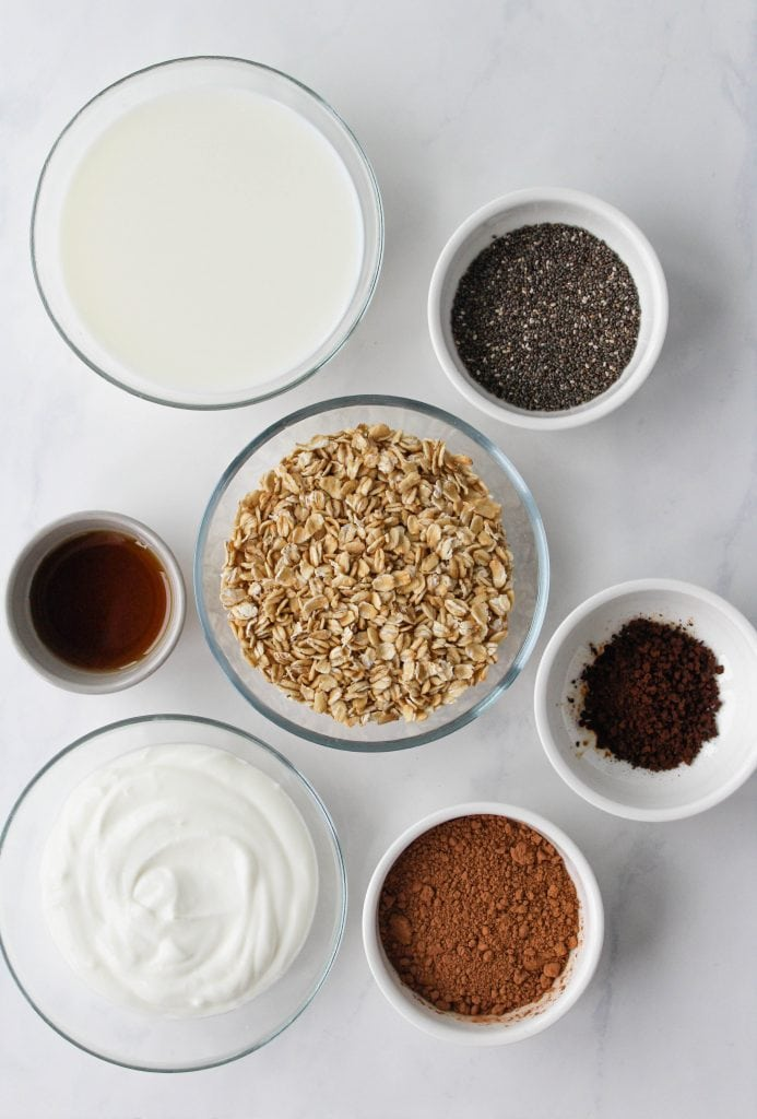 Recipe ingredients measured out into bowls on a white marble surface.
