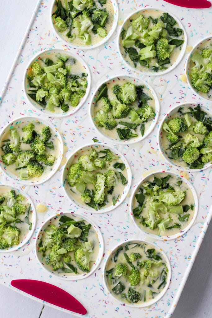 A silicone muffin pan with each slot filled with egg mixture, spinach and broccoli