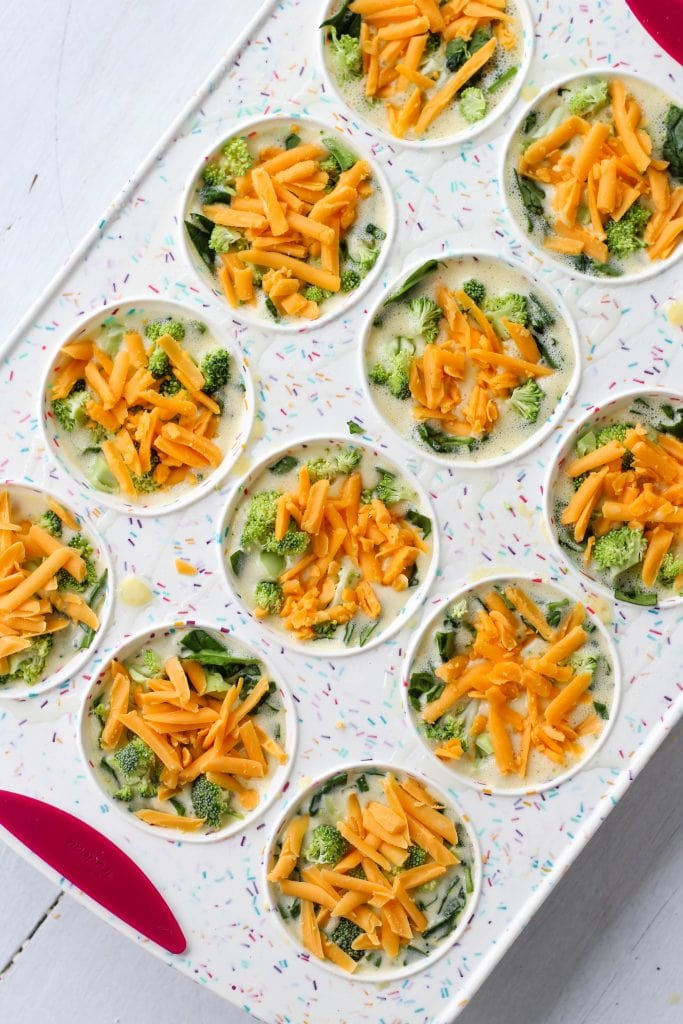 A silicone muffin pan with each slot filled with egg mixture, spinach, broccoli and cheddar cheese
