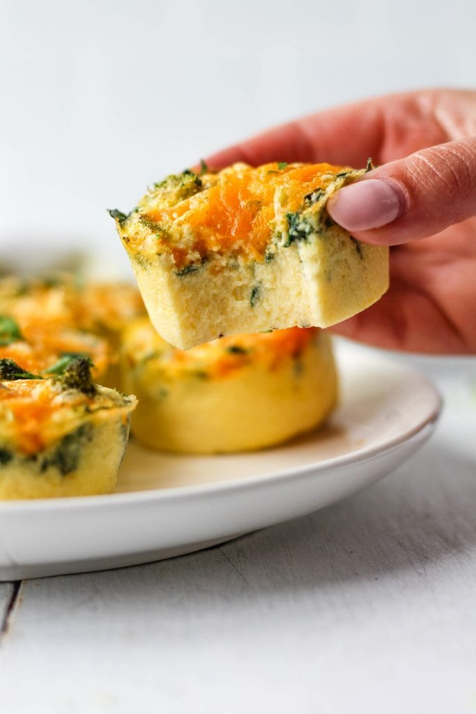 A hand holding a broccoli cheddar baked egg bite with a single bite taken out of it.