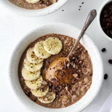 Mocha overnight oats in a white speckled bowl, on a white marble surface, topped with sliced bananas, peanut butter and chopped chocolate.