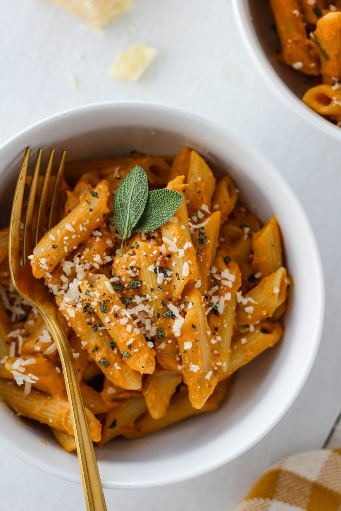 Pumpkin sage pasta in a white bowl with a gold fork on a white background.