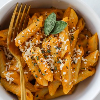 Penne pasta with creamy pumpkin sage pasta sauce garnished with sage leaves and parmesan cheese in a white bowl.